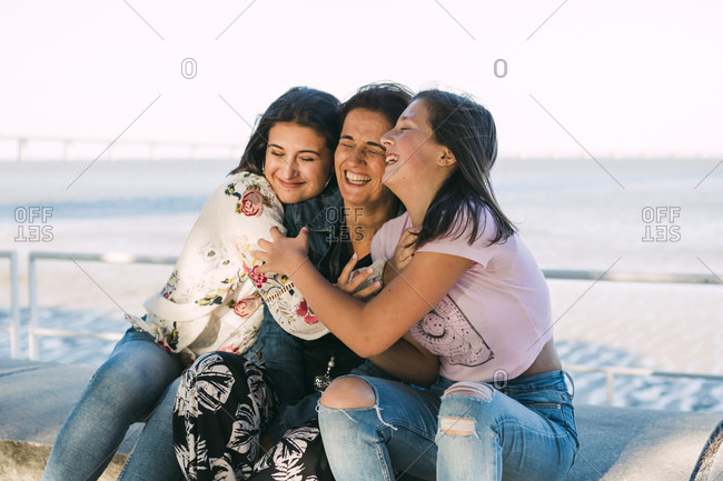 Loving daughters embracing cheerful mother while sitting on retaining wall against sea