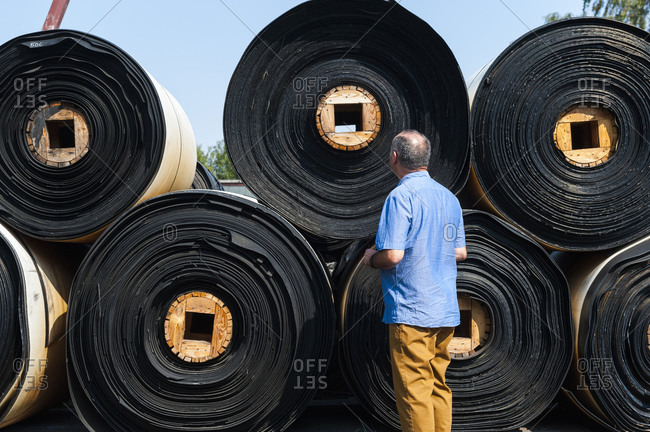 Senior man checking product on yard of a rubber processing factory