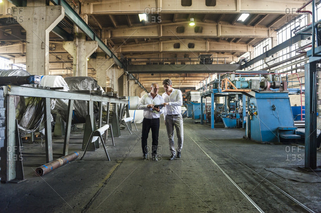 Two businessmen having a meeting looking at tablet in a factory hall