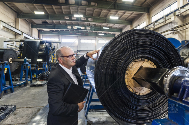 Senior businessman examining product in a rubber processing factory