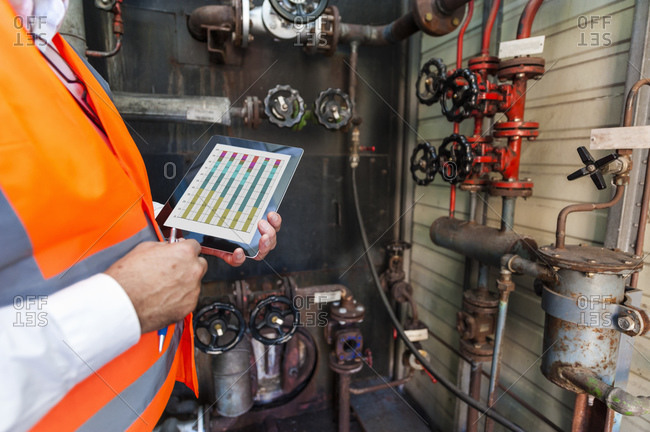 Man with tablet wearing safety vest examining a machine