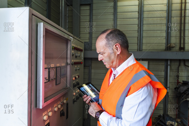 Senior man with tablet wearing safety vest examining a machine