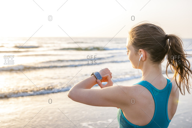 Sporty woman checking her smartwatch at the sea