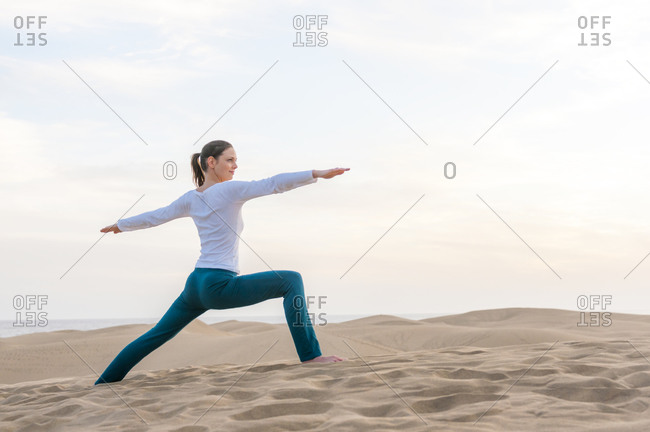 Woman practicing yoga at sunset in the dunes- Gran Canaria- Spain