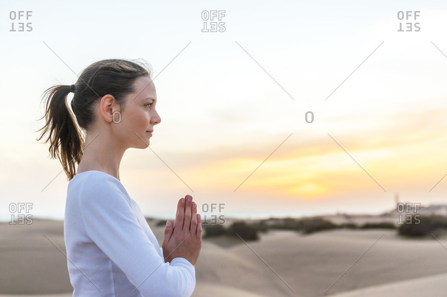 Woman meditating at sunset in the dunes- Gran Canaria- Spain
