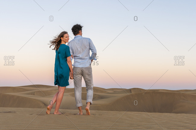Affectionate couple walking in the dunes at sunset- Gran Canaria- Spain