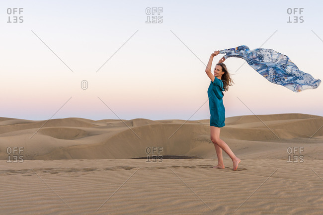 Happy woman holding cloth at sunset in the dunes- Gran Canaria- Spain