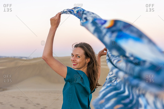 Portrait of happy woman holding cloth at sunset in the dunes- Gran Canaria- Spain