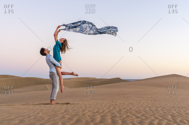 Carefree couple at sunset in the dunes- Gran Canaria- Spain