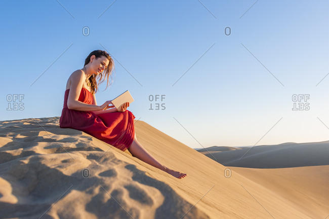 Woman in red dress sitting in the dunes using tablet- Gran Canaria- Spain