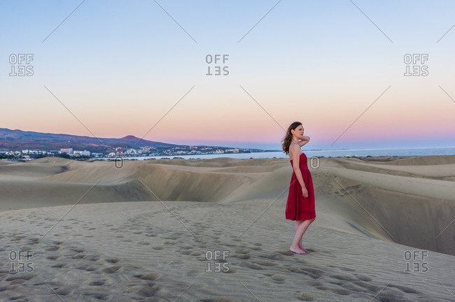 Woman in red dress at sunset in the dunes- Gran Canaria- Spain