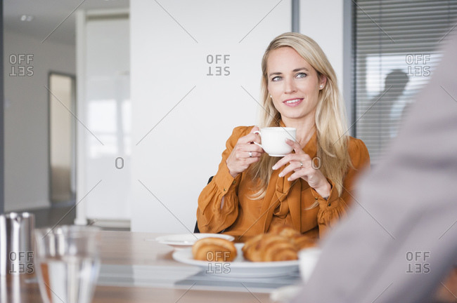 Beautiful businesswoman holding coffee cup while sitting at conference table in board room