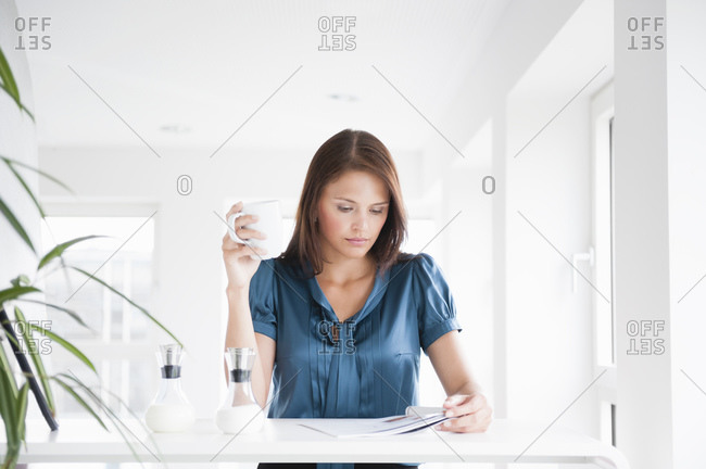Businesswoman holding coffee cup while reading magazine at desk in office