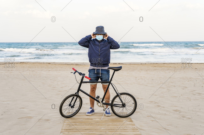 Mature man with bicycle- standing on the beach- wearing face mask