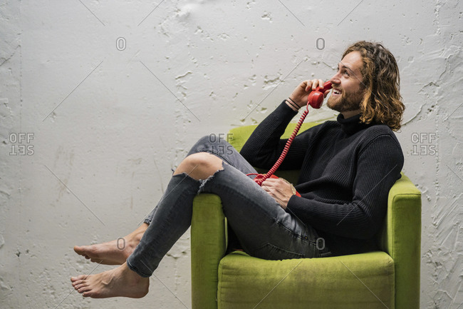 Smiling man talking over telephone while sitting on armchair against wall at home