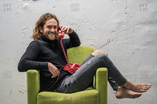 Smiling man talking over telephone while relaxing on armchair against wall