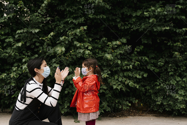 Mother and daughter wearing masks while playing clapping game against plants