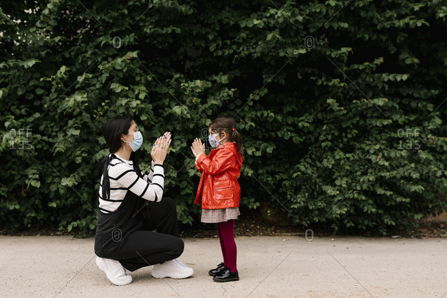 Mother and daughter wearing masks while playing clapping game on street