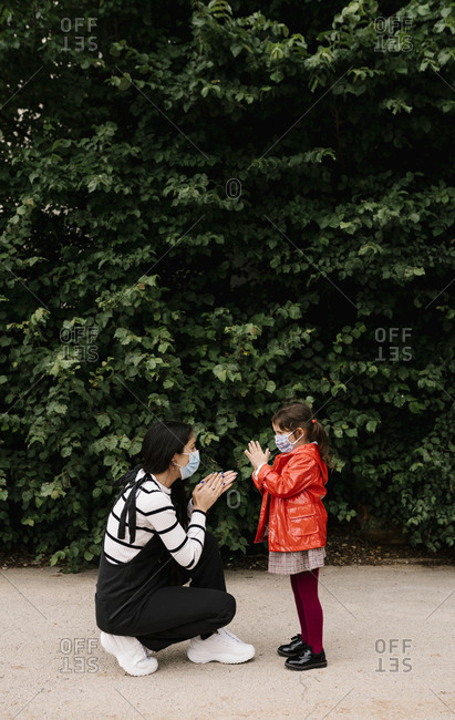 Mother and daughter wearing masks while playing clapping game outdoors