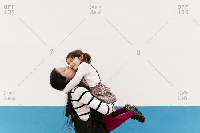 Mother kissing daughter on cheek against wall during sunny day