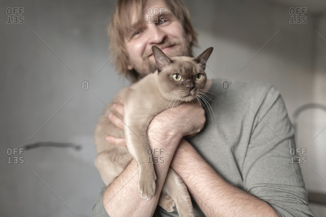 Happy man carrying Burmese cat during home renovation