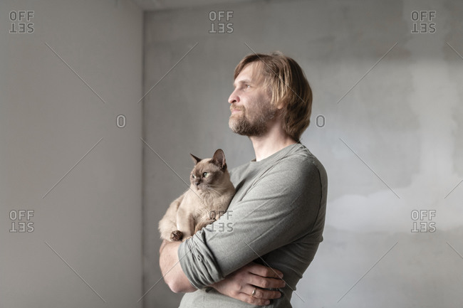 Thoughtful man carrying Burmese cat during home renovation