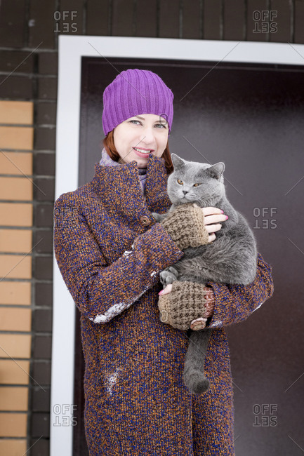 Beautiful woman in warm clothing carrying British Shorthair cat outside front door