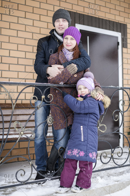 Cute girl standing with parents outside house during winter
