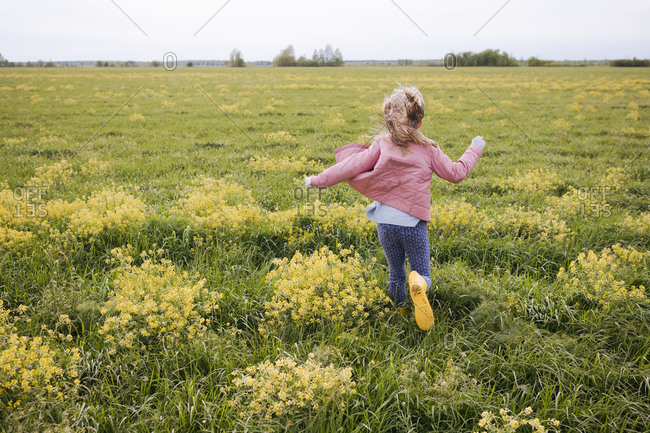 Girl in yellow rubber boots running near rape field