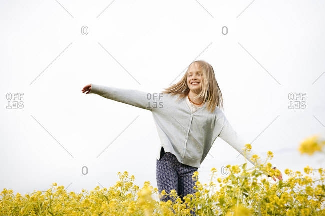 Smiling girl walking on rapeseed flowers