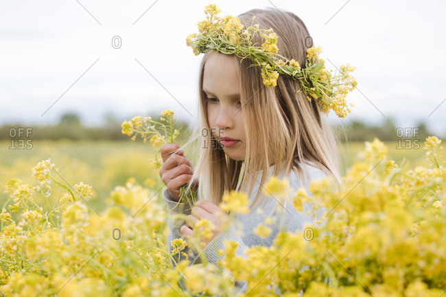 Portrait of girl with wreath of rapeseed flowers