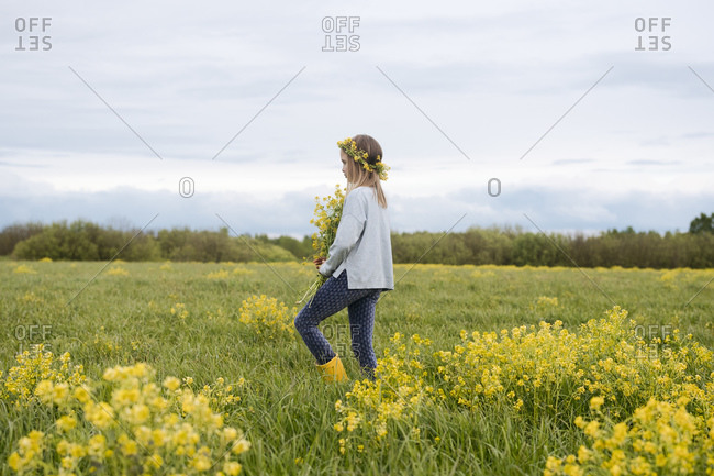 Girl walking with bouquet of rapeseed flowers on rape field