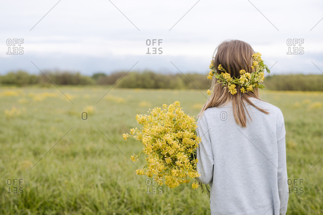 Rear view of girl with wreath and rapeseed flowers