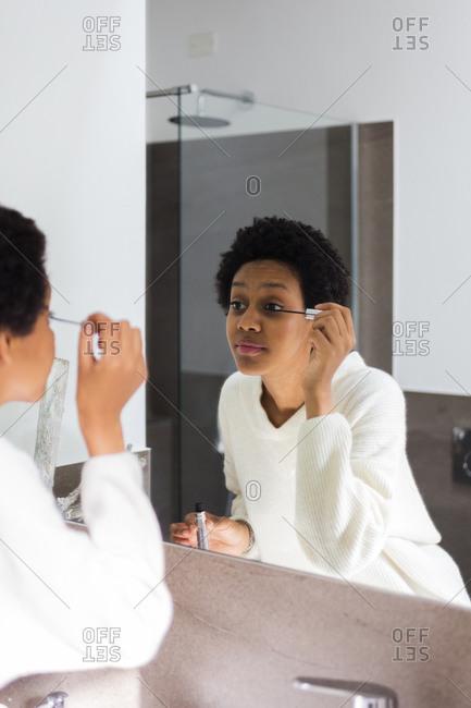 Mirror image of young woman applying mascara