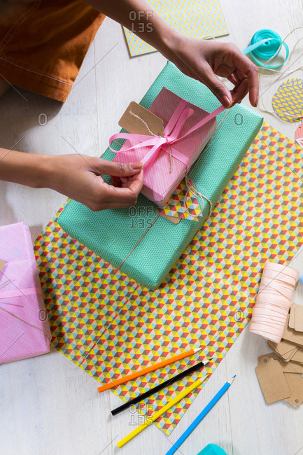 Hand of young woman wrapping present