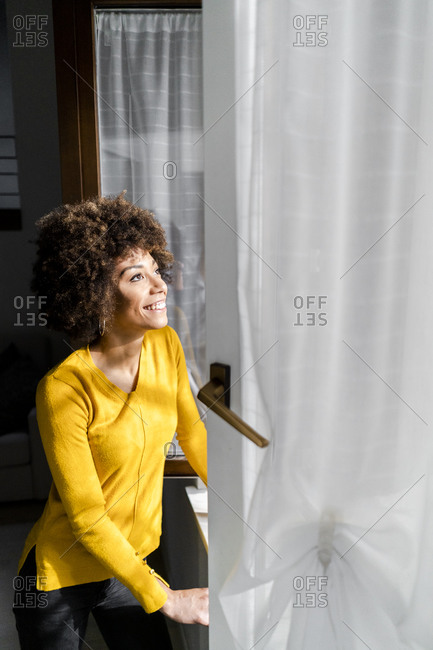 Portrait of happy young woman standing at open window looking up