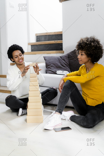 Smiling young woman stacking boxes on the floor at home while her friend watching her