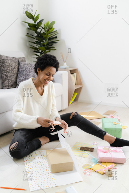 Smiling young woman sitting on the floor at home wrapping presents