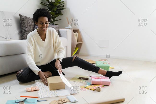 Smiling young woman sitting on the floor at home wrapping present