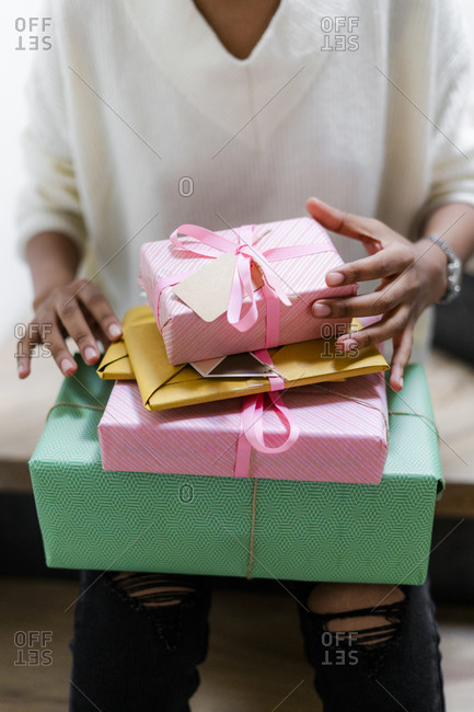 Young woman with stack of wrapped gifts