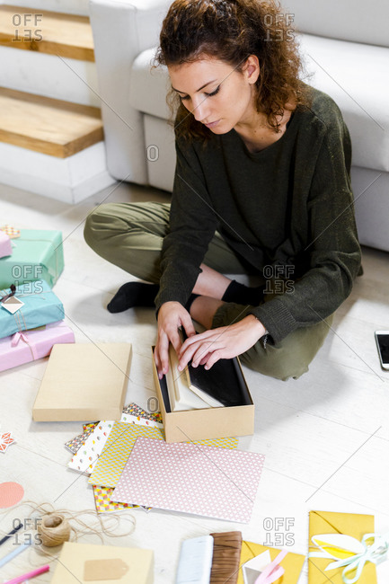 Young woman sitting on the floor at home wrapping gift