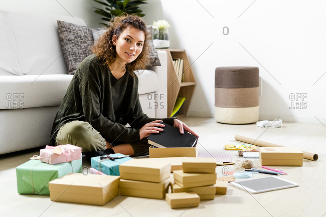 Portrait of smiling young woman sitting on the floor at home wrapping gifts