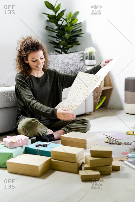 Smiling young woman sitting on the floor at home wrapping gifts