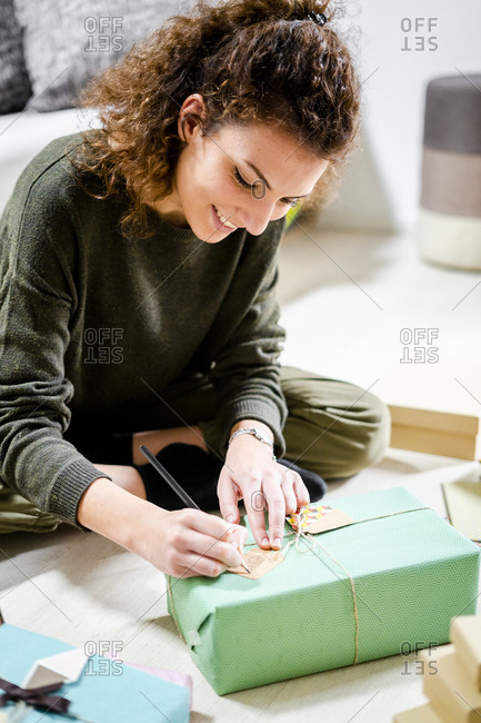 Smiling young woman sitting on the floor at home writing on present tag