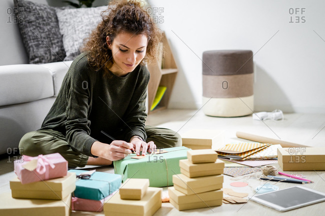 Young woman sitting on the floor at home writing on present tag