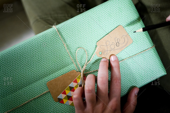 Hand holding tag with the word 'Love' on wrapped gift