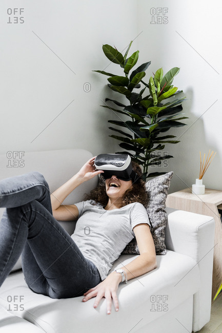 Young woman lying on couch at home using Virtual Reality Glasses