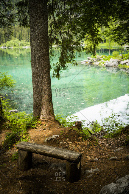 Italy- Province of Udine- Tarvisio- Simple wooden bench on shore of Fusine Lake