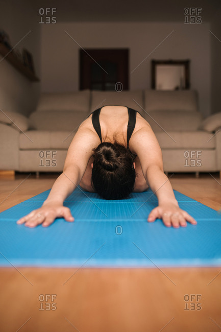 Woman exercising on mat in living room at home