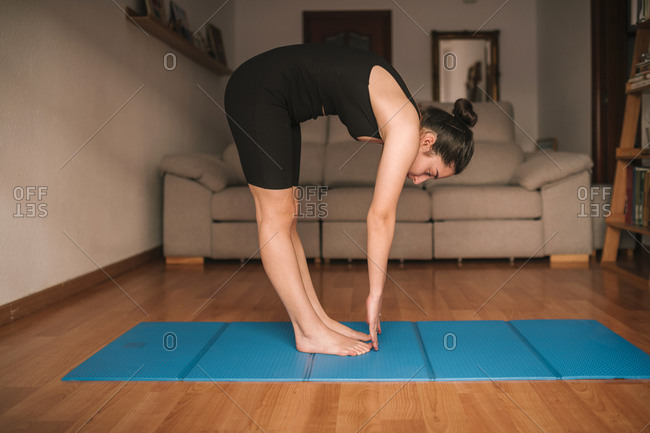 Young woman bending while practicing yoga in living room at home